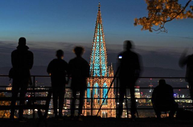 Warga menikmati pemandangan menara menara Gereja Freiburger Muenster, Freiburg, Jerman, (13/10/2018). Setelah 12 tahun restorasi, perancah yang melingkupinya dicopot bersamaan Festival Turmfinale. AFP Photo/DPA/Patrick Seeger