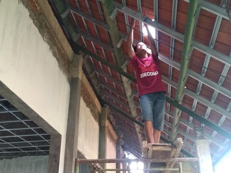 Seorang tukang menurunkan genting yang sudah terpasang dalam pembangunan ruang kelas baru. Medcom.id/Syaikhul Hadi
