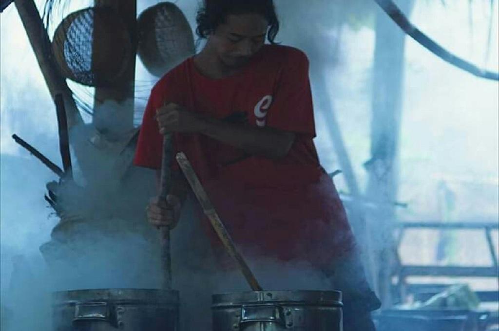 Ahmad Karomi, pemilik Sanggar Omah Petruk di Jepara, menyiapkan larutan dari kulit kayu mahoni untuk mewarnai kain tenun Troso di Jepara, Medcom.id - Rhobi Shani