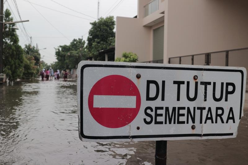Warga mencoba melintasi banjir yang terjadi di Komplek TNI AL. Medcom.id/Antonio