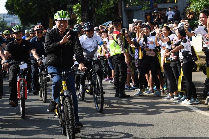 Presiden Joko Widodo menyapa warga ketika bersepeda menuju lokasi penyambungan instalasi listrik PLN gratis melalui sinergi BUMN untuk masyarakat di Bogor, Jawa Barat. Antara/Wahyu Putro A