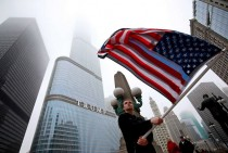 Seorang wargamengibarkan bendara Amerika Serikat dalam peringatan setahun pemerintahan Presiden Trump. Aksi berlangsung di depan Trump Tower, Chicago. AFP Photo/Jim Young