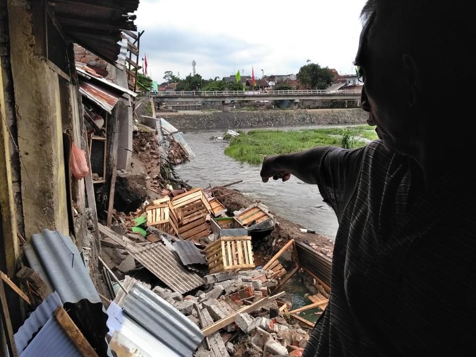 Seorang warga menunjukkan lokasi talut yang ambrol. Medcom.id/Ahmad Mustaqim