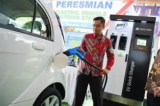Petugas mendemonstrasikan cara pengisian kendaraan listrik