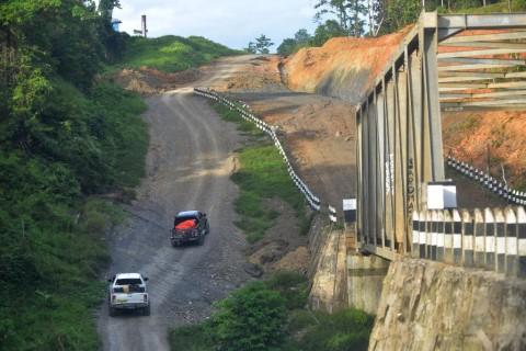 Kendaraan melintasi ruas jalan trans Papua Barat yang melintasi