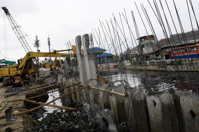Ilustrasi. Pekerja menggunakan alat berat menyelesaikan pemasangan dinding turap di Kali Sentiong, Kemayoran, Jakarta, Senin (26/11/2018) - ANT/Wahyu Putro A.