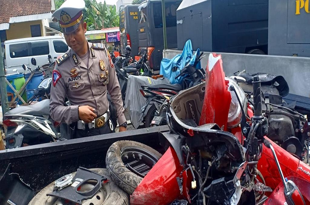 Seorang polisi menunjukkan kendaraan yang rusak akibat ditabrak mobil jenis pick up, Medcom.id - Mustaqim