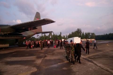 Prajurit TNI dan Polri menurunkan peti jenazah korban penembakan