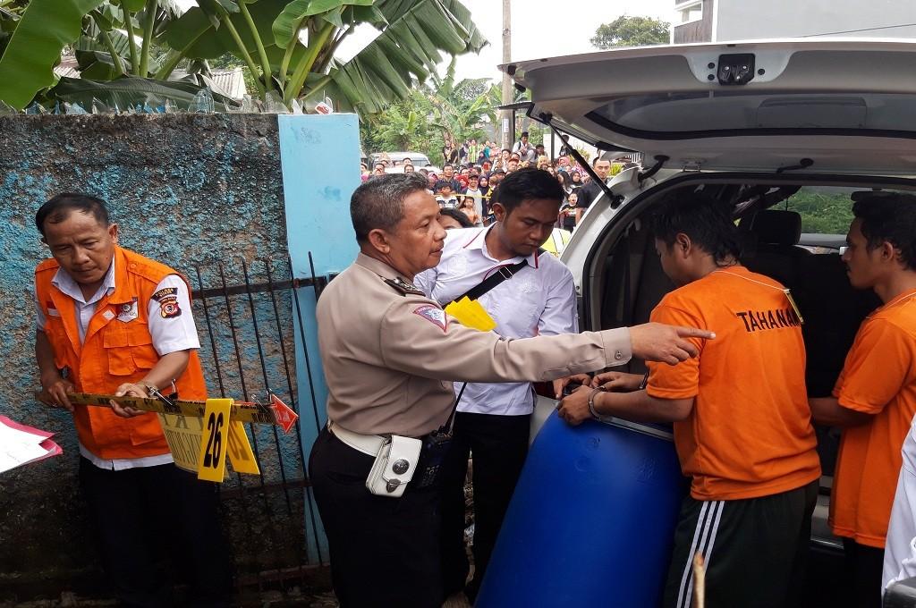 Tersangka membawa drum biru, yang menjadi tempat menyimpan jenazah Dufi lalu membuangnya di Kabupaten Bogor, Medcom.id - Rizky Dewantara