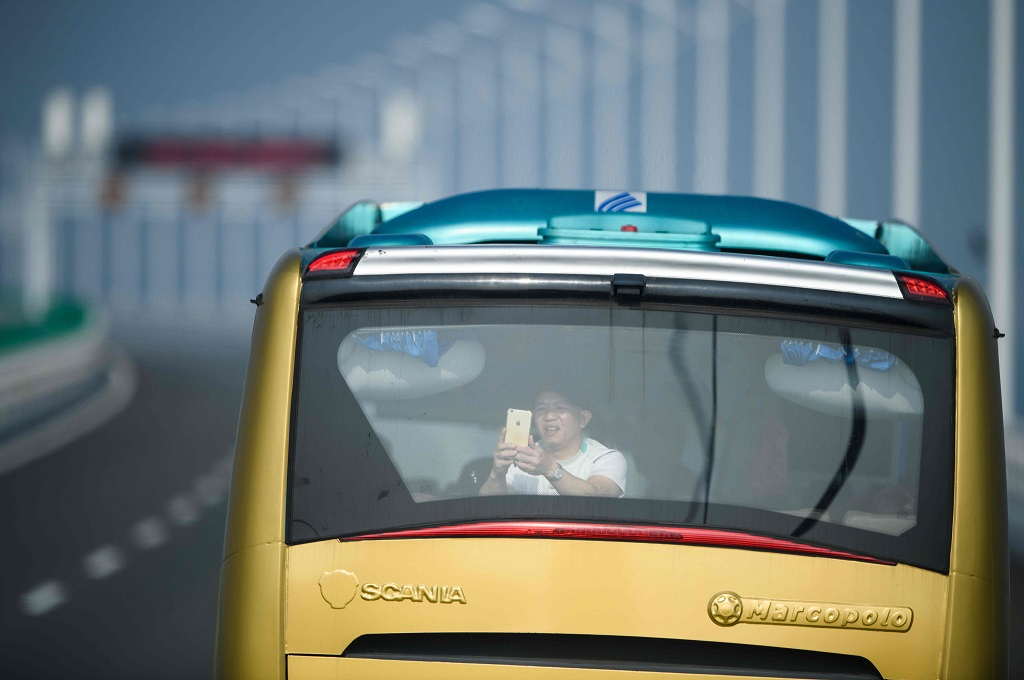 Seorang penumpang mengambil foto saat menaiki sebuah bus menuju Hong Kong, 24 Oktober 2018. (Foto: AFP/ANTHONY WALLACE)