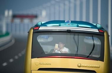 Seorang penumpang mengambil foto saat menaiki sebuah bus menuju