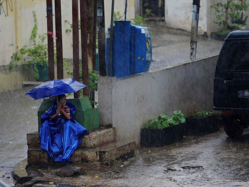 Seorang anak menggunakan jas hujan dan payung duduk di pinggir jalan di Jl KH Mas Mansyur, Jakarta Pusat. Foto: MI/Rommy Pujianto.