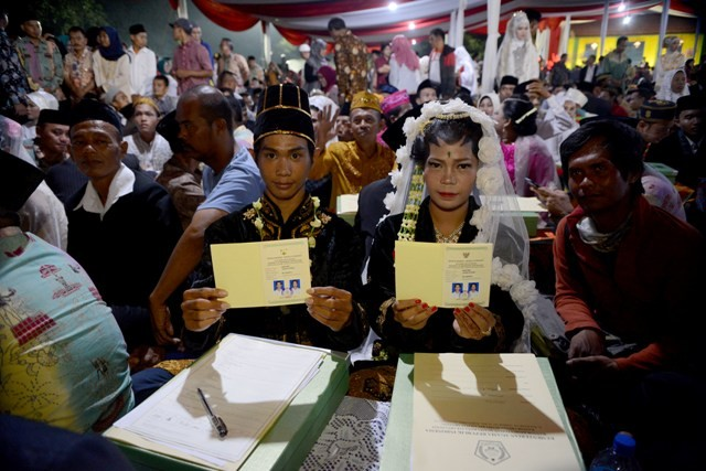 Pasangan calon pengantin mengucapkan ijab kabul didepan pengulu saat mengikuti nikah massal di area Park and Ride, Thamrin, Jakarta, Minggu (31/12). Foto: MI/Susanto