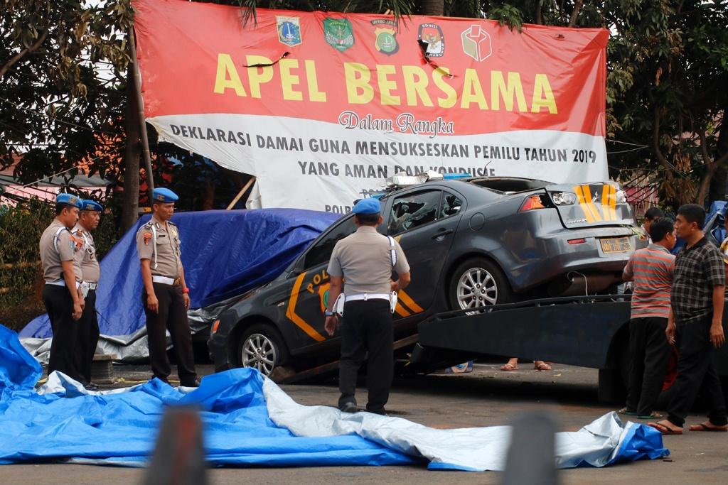 Polisi melihat kendaraan yang dirusak massa di Polsek Ciracas, Jakarta Timur, Rabu (12/12/2018). Foto: MI/Bary Fathahilah