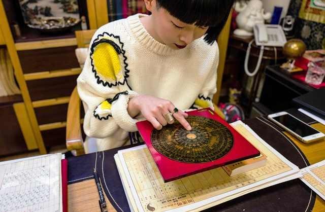 Seorang ahli feng shui di Hong Kong sedang menghitung potensi peruntungan klien. AFP Photo/Elaine Yu