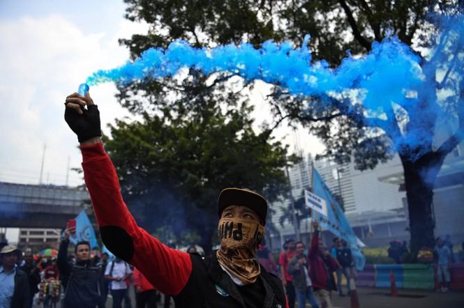 Massa dari berbagai elemen buruh berjalan kaki menuju Balai Kota Jakarta, Selasa, 18 Desember 2018.