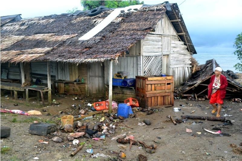 arga berjalan di samping atap rumah miliknya yang roboh setelah diterjang gelombang tinggi di Kampung Cikadu, Kecamatan Tanjung Lesung, Pandeglang, Minggu (23/12/18). ANTARA FOTO/Muhammad Bagus Khoirunas.