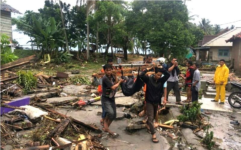 Petugas Basarnas dibantu warga mengevakuasi korban meninggal akibat tsunami di pesisir Cinangka, Serang, Banten, Minggu (23/12). ANTARA FOTO/Basarnas.