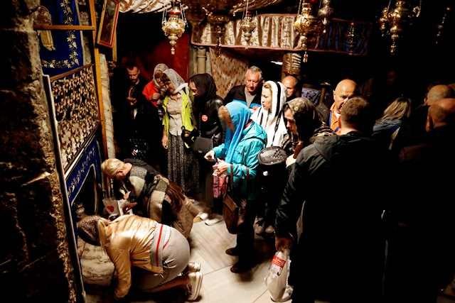 Jemaat menunggu giliran menziarahi ceruk di dalam gua yang diyakini tempat peraduan Yesus Kristus ketika lahir. Bangunan gereja dibangun tepat di atas gua sakral tersebut. AFP Photo/Thomas Coex