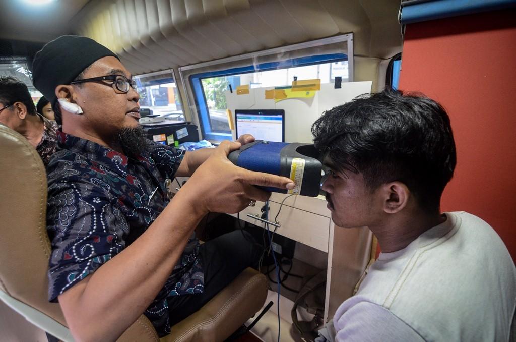 Petugas Disdukcapil Kota Bandung merekam KTP elektronik di Kampus Universitas Islam Bandung, Bandung, Jawa Barat, Kamis (27/12/2018). Foto: Antara/Raisan Al Farisi