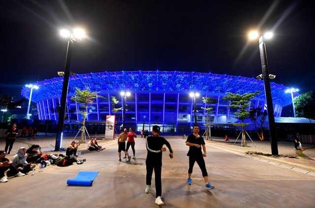 Warga berolahraga di pelataran SU GBK yang bermandi cahaya warna biru. Seluruh venue Asian Games 2018 dilengkapi fasilitas ramah penyandang cacat sesuai standart internasional. AFP Photo/Adek Berry