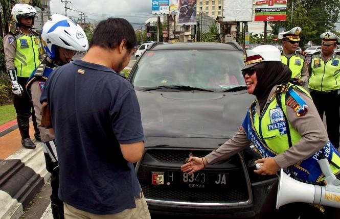 Polisi menegur seorang pengemudi mobil yang kendaraannya menggunakan pelat nomor tidak sesuai spesifikasi, saat operasi keselamatan lalu lintas di Semarang, Jawa Tengah, Selasa, 13/3. ANTARA FOTO/R. Rekotomo.