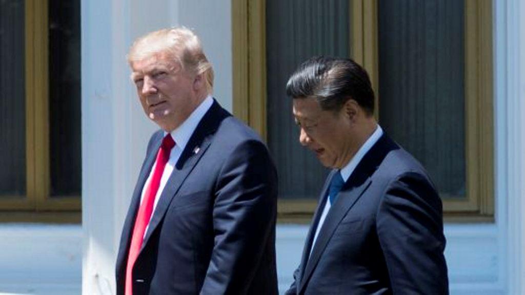 Presiden Donald Trump (kiri) dan Presiden Tiongkok Xi Jinping berjalan bersama (Jim Watson/AFP)