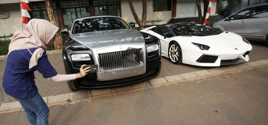 Jurnalis mengamati mobil mewah Rolls-Royce dan Lamborghini milik Raffi Ahmad yang diparkir di dekat masjid perumahannya di Green Andara Residences, Jakarta Selatan. Foto: MI/Arya Manggala.
