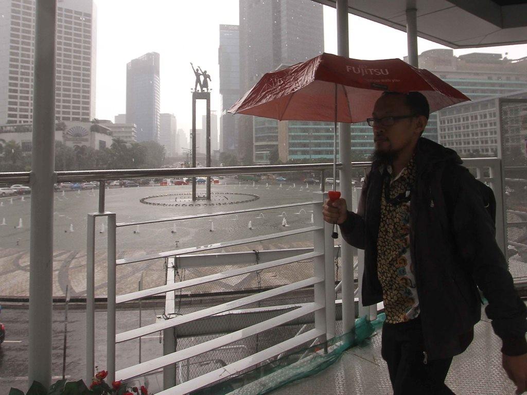Masyarakat melintas dengan membawa payung saat hujan di kawasan Bundaran HI, Jakarta. Foto: MI/Angga Yuniar.