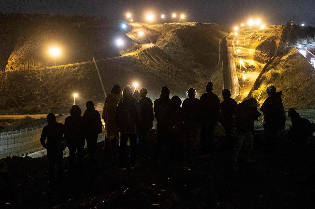 Sekelompok imigran bersiap menyeberangi perbatasan dari Tijuana ke San Diego, AS, pada malam pergantian tahun, 31 Desember 2018. (Foto: AFP/GUILLERMO ARIAS)