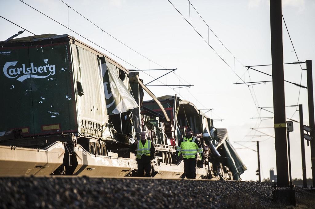 Dua petugas berada di dekat kereta kargo yang rusak dalam kecelakaan di Denmark, 2 Januari 2019. (Foto: AFP/Ritzau Scanpix/TIM K. JENSEN)