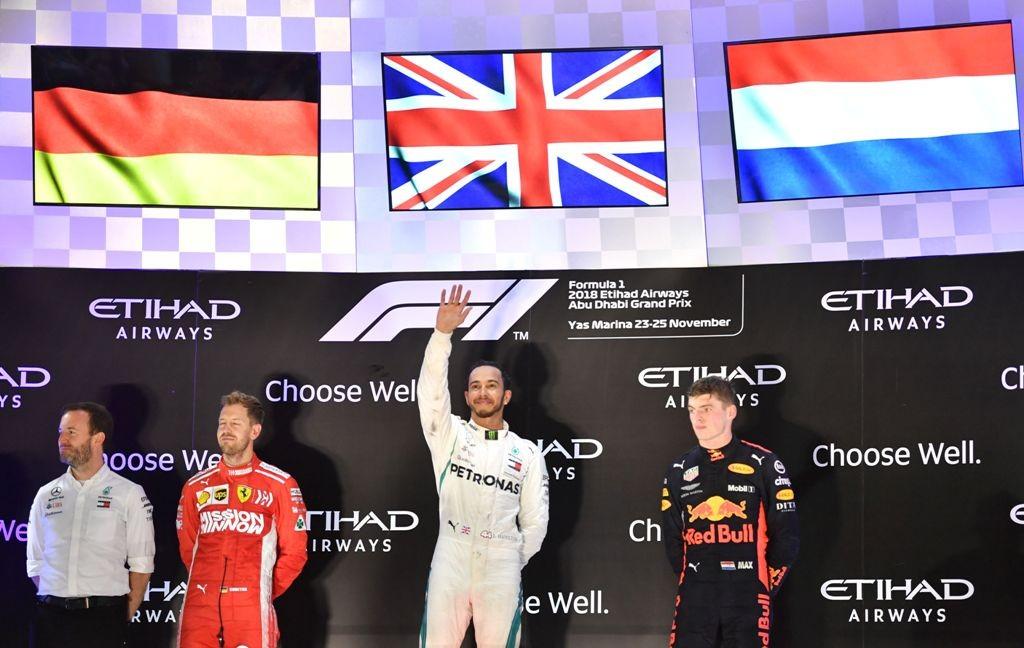 Lewis Hamilton berdiri di podium utama usai memenangi GP F1 Abu Dhabi tahun 2018 (Foto: Andrej ISAKOVIC / AFP)