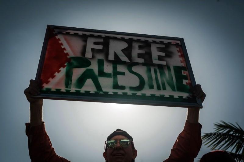 Salah seorang warga yang mendukung kemerdekaan Palestina melakukan aksi protesnya. (Foto: AFP).
