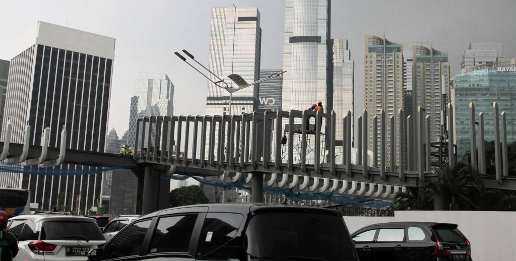 Pekerja menyelesaikan proyek pembangunan revitalisasi jembatan penyeberangan orang (JPO) di depan Ratu Plaza, Jalan Jend. Sudirman, Jakarta. Foto: MI/Pius Erlangga.