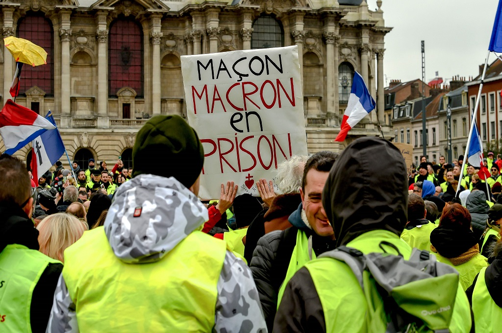 Demonstran rompi kuning membawa spanduk bertuliskan Macron di Penjara dalam unjuk rasa di Lille, Prancis, 5 Januari 2019. (Foto: AFP/PHILIPPE HUGUEN)
