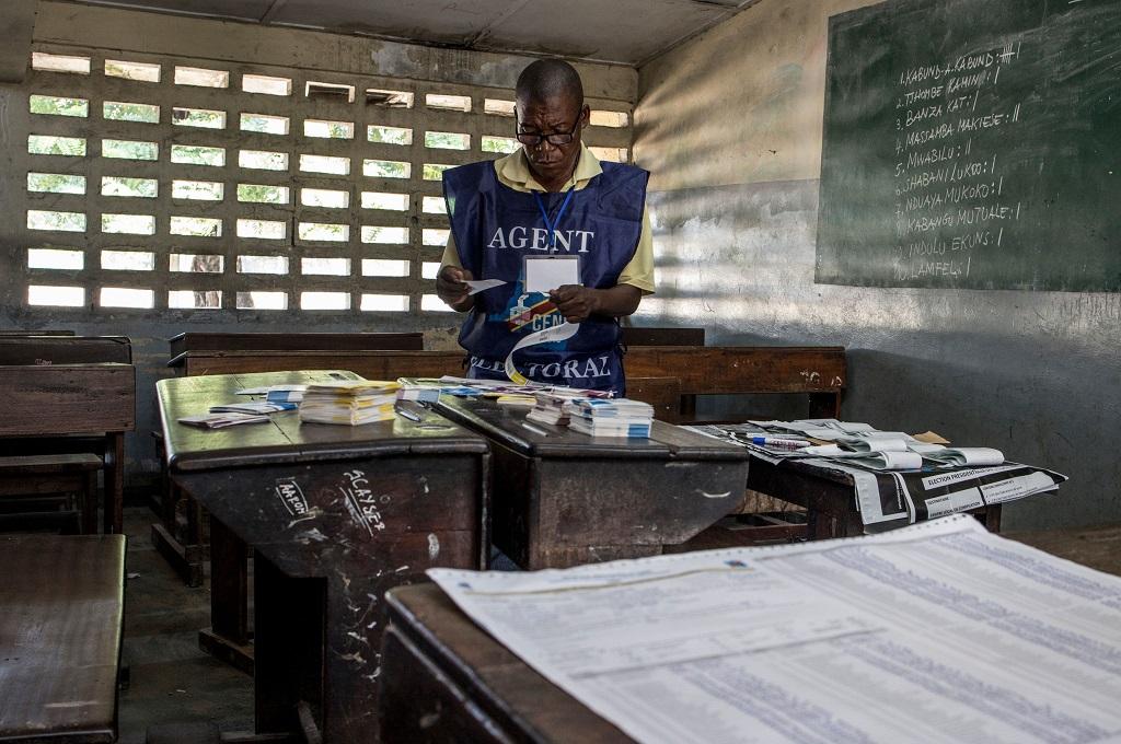 Petugas merapikan kertas suara di Kinshasa, RD Kongo, 31 Desember 2018, setelah berlangsungnya pilpres. (Foto: AFP/MARCO LONGARI)