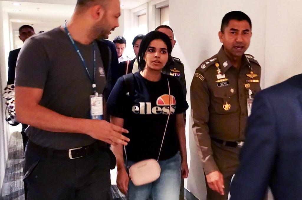 Rahaf Mohammed al-Qunun (tengah) dikawal petugas imigrasi Thailand (kanan) dan pejabat UNHCR di Bandara Suvarnabhumi di Bangkok, Thailand, 7 Januari 2019. (Foto: AFP/Handout/Thai Immigration Bureau)