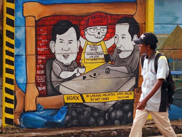 Warga melintas di dekat gambar mural capres Joko Widodo dan Prabowo Subianto di Jalan Juanda, Depok, Jawa Barat. Foto: MI/Bary Fathahilah.