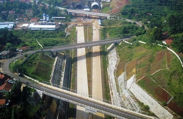 Foto udara terowongan kembar proyek Jalan Tol Cileunyi-Sumedang-Dawuan (Cisumdawu) di Sumedang, Jawa Barat. Keberadaan jalan tol memicu bermunculannya perumahan baru di sekitar akses masuk dan keluarnya. Antara Foto/Raisan Al Farisi