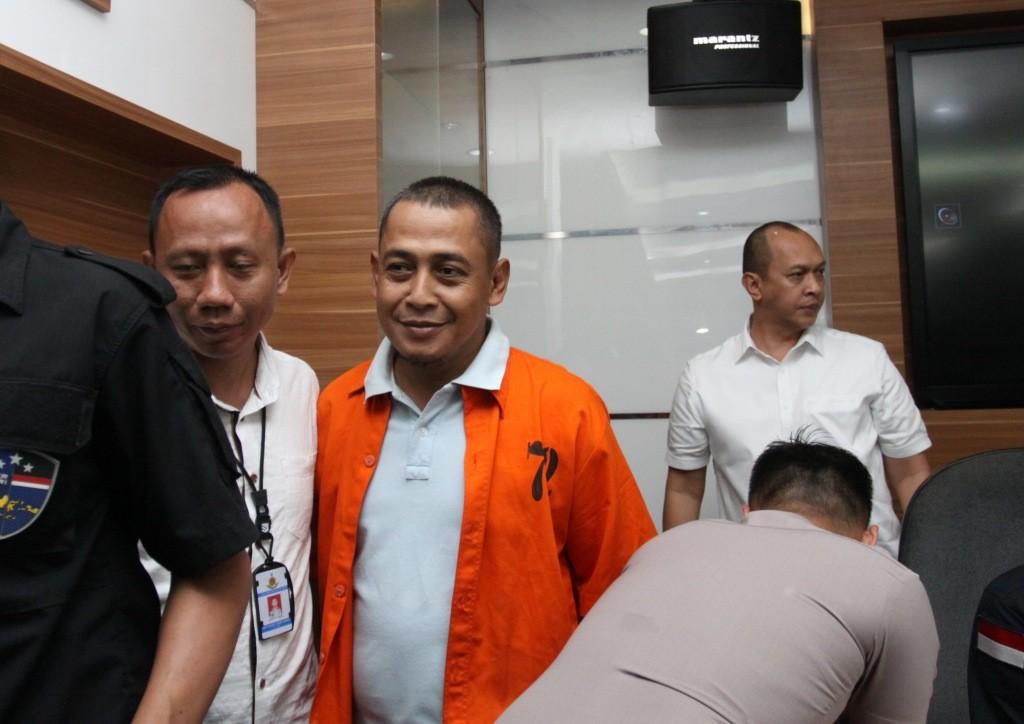 Polisi menggiring BBP (tengah), tersangka kasus berita hoax saat Rilis berita hoax 7 kontainer surat suara tercoblos, di Divisi Humas, Mabes Polri, Jakarta. Foto: Antara/Reno Esnir.