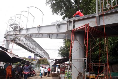 Pekerja menyelesaikan pembangunan jembatan penyeberangan orang