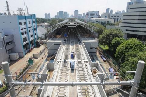 Pekerja menyelesaikan pembangunan jalur dan stasiun Mass Rapid