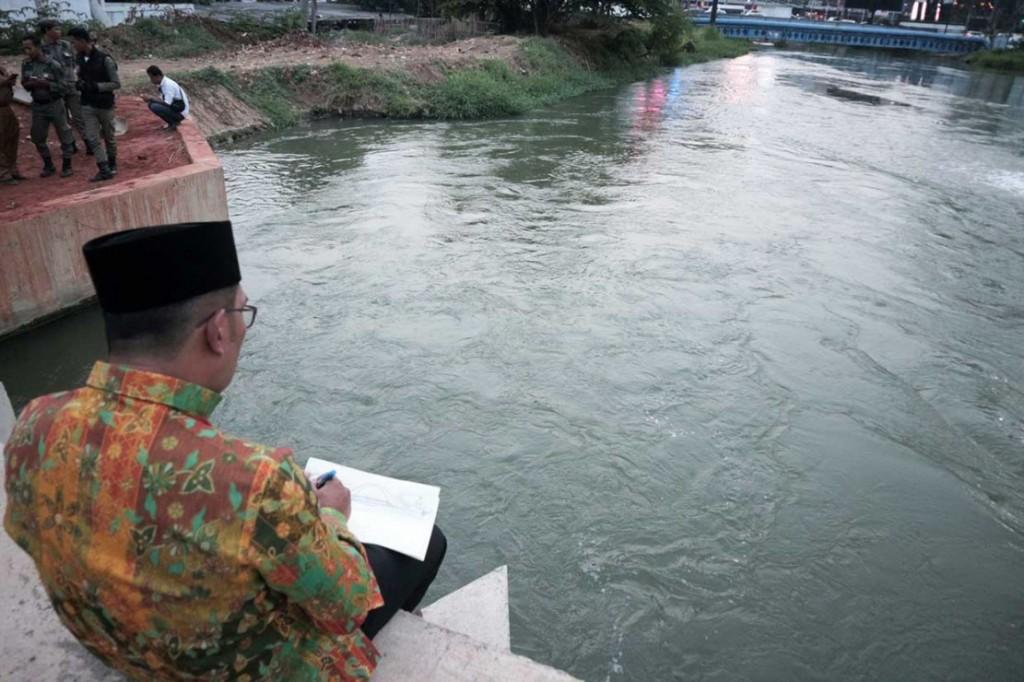 Gubernur Jawa Barat Ridwan Kamil tengah menggambar sketsa revitalisasi Kalimalang, Bekasi, Jawa Barat. Medcom.id/Antonio