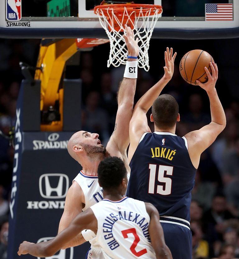 Center Denver Nuggets, Nikola Jokic (15), mencoba memasukkan bola ke ring meski dihalangi dua pemain LA Clippers (AFP/Matthew Stockman)