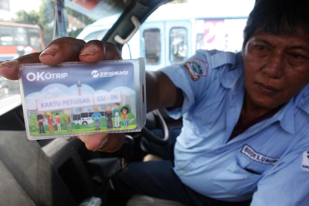 Supir Angkot Ok Otrip (kini beralih nama menjadi Jak Lingko) menunjukkan kartu OK Otrip saat menunggu penumpang di Terminal Kampung Melayu, Jakarta. MI/Barry Fathahilah.