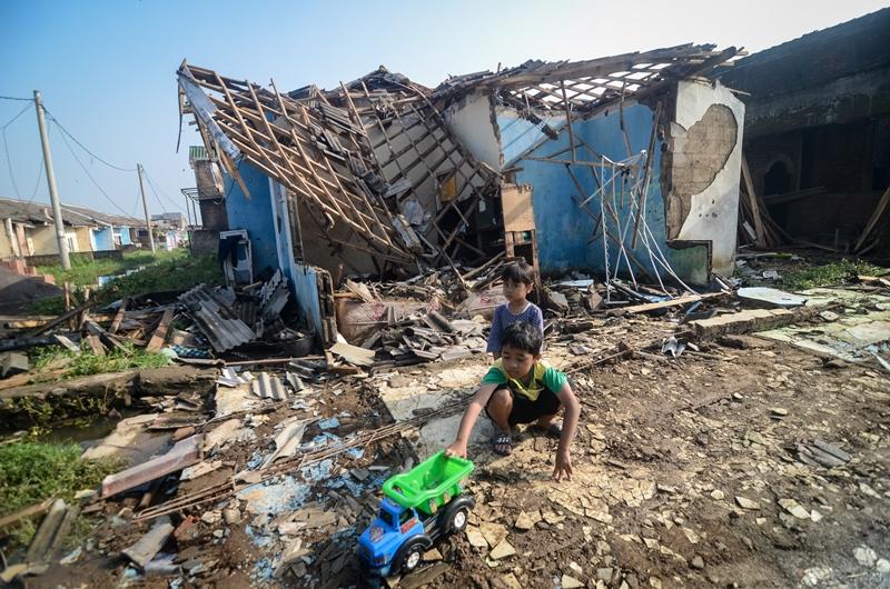 Dua anak bermain di depan rumah yang rusak akibat puting beliung yang menerjang Kabupaten Bandung, Jawa Barat, pada 11 Januari 2019. Antara/Raisan Al Farisi
