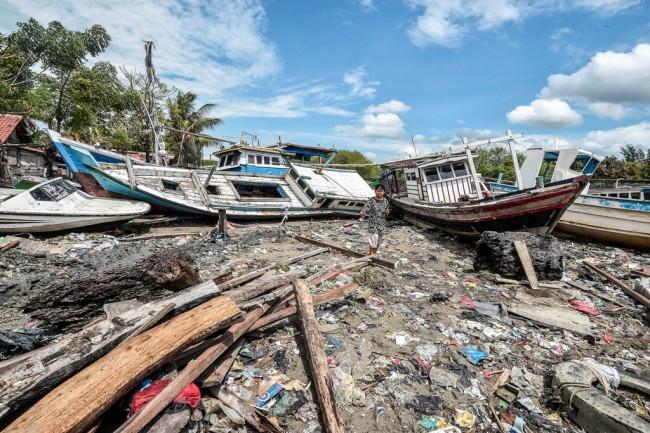 Ilustrasi--Warga melintas di antara kapal yang terdampar ke pemukiman penduduk akibat gelombang tsunami di desa Sukamanah, Anyer. ANT/M Adimaja.