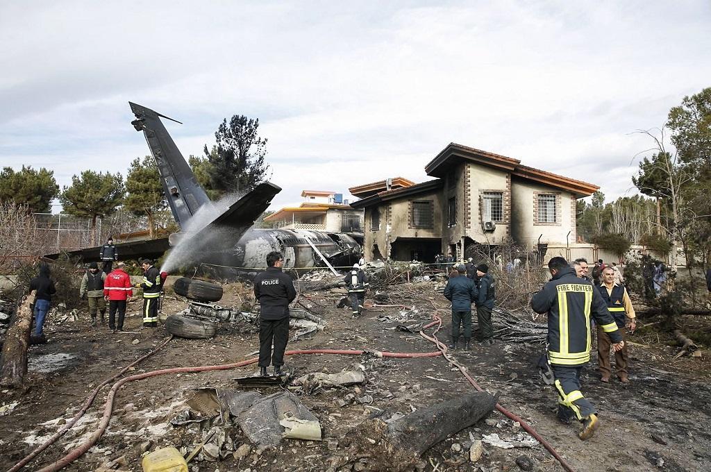 Petugas keamanan dan pemadam berada di lokasi kecelakaan pesawat kargo di dekat Teheran, Iran, 14 Januari 2019. (Foto: AFP/HASAN SHIRVANI)