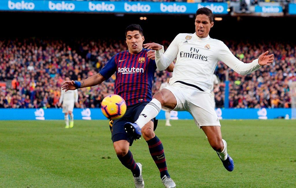 Momen saat penyerang Barcelona Luis Suarez (kiri) berduel dengan bek Real Madrid Raphael Varane (kanan) pada El Clasico jilid pertama musim 2018--2019 (Foto: AFP/Josep Lago)