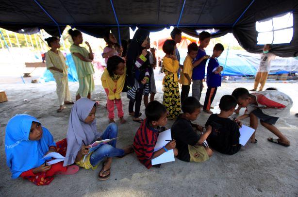 Anak pengungsi belajar di tenda darurat, di pengungsian lapangan Watulemo, kantor Walikota Palu, Selawesi Tengah, MI/Ramdani.